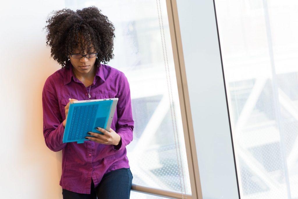 woman in purple dress shirt using laptop